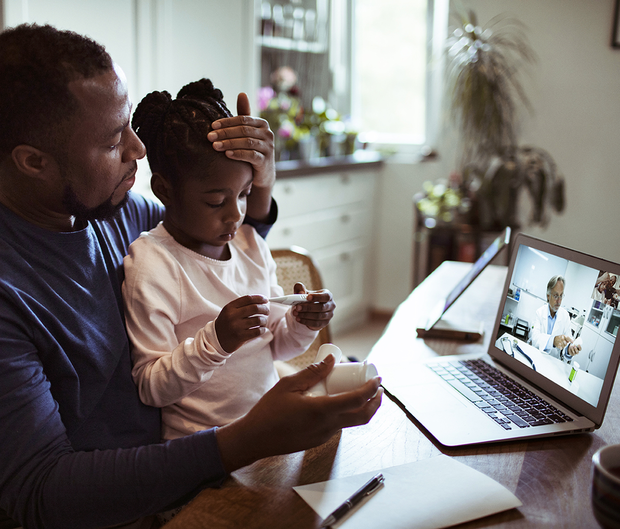 Father having online consult with doctor about poorly daughter