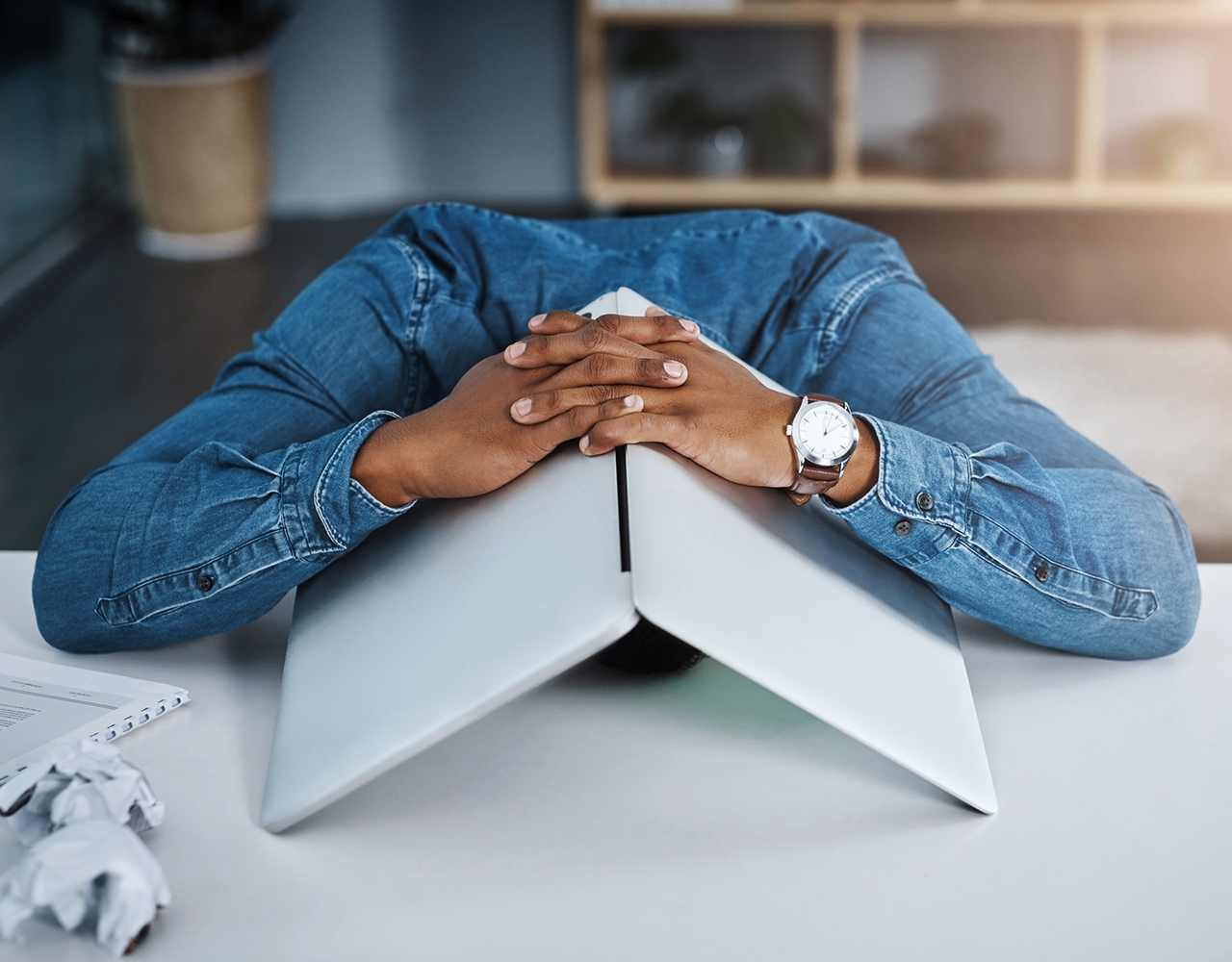 Man with his head under a laptop