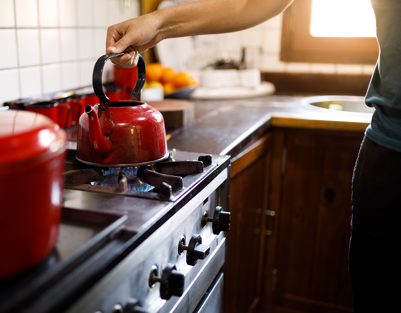 Close up of kettle boiling on a gas stove