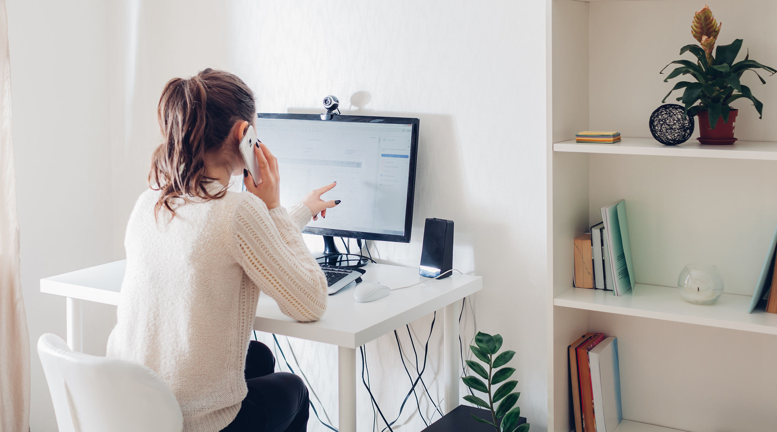 Woman working from home sitting at desk while on phone and pointing to computer screen