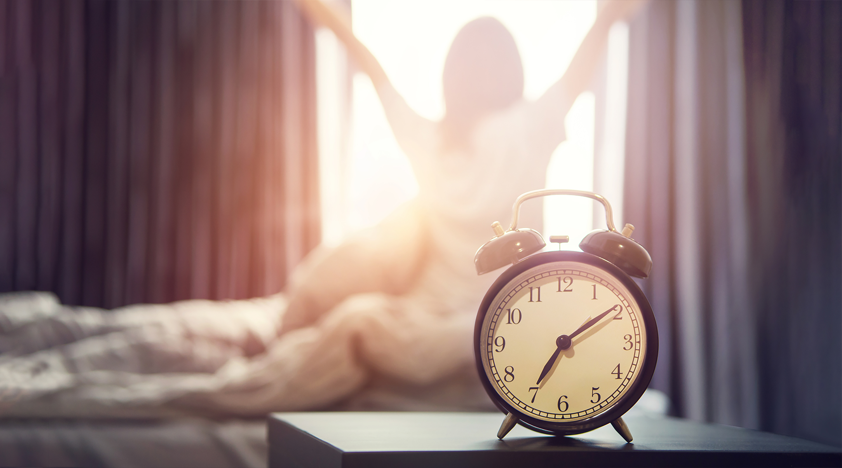 Close up of alarm clock in a bedroom with woman waking up in the background