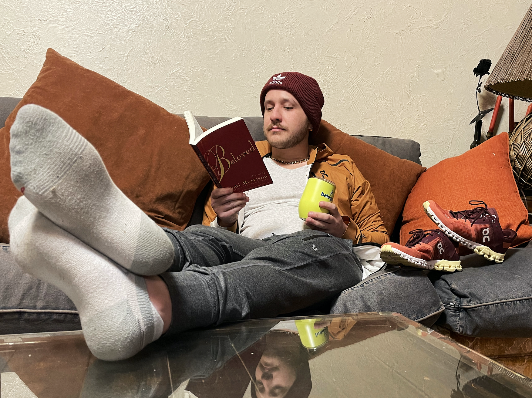 man lounging on a couch with his feet propped on a table reading a book with his shoes sitting next to him