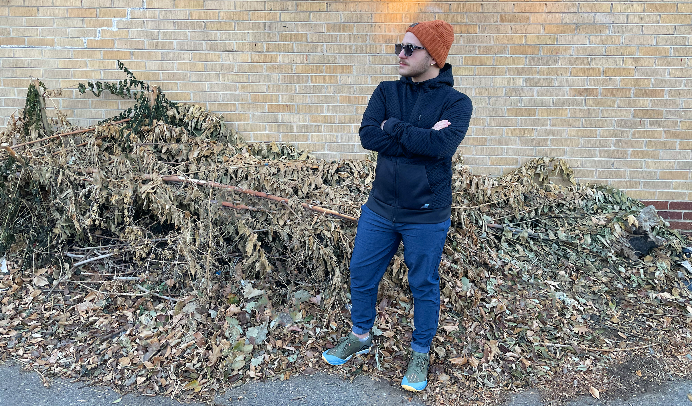 man in front of a building with a lot of fallen leaves wearing an orange beanie, blue jacket, blue pants, and olive sneakers and sunglasses