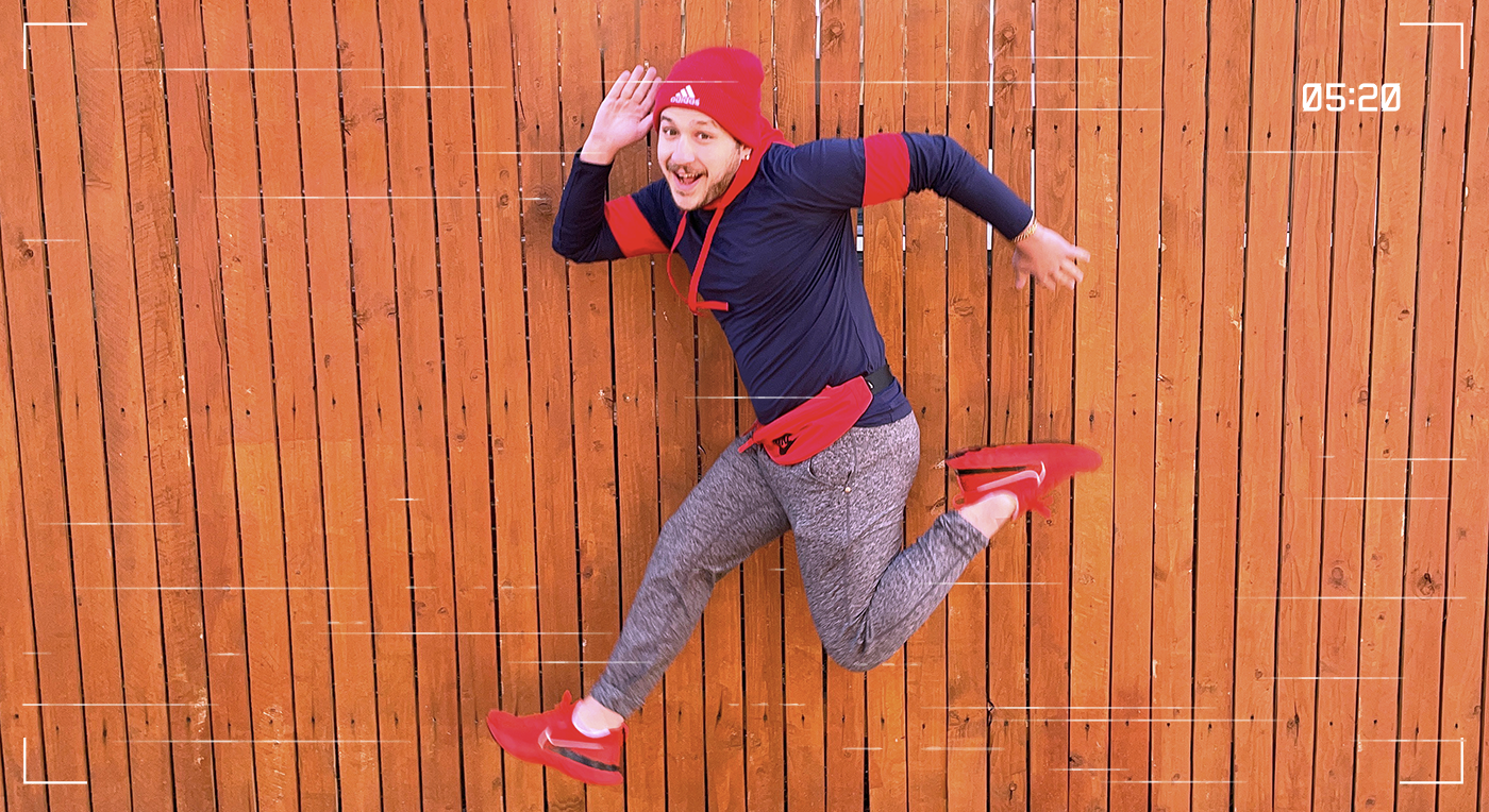 Image of man jumping in front of a fence wearing a red beanie, blue and red hoodie, a red fanny pack, grey sweatpants, and red nike sneakers