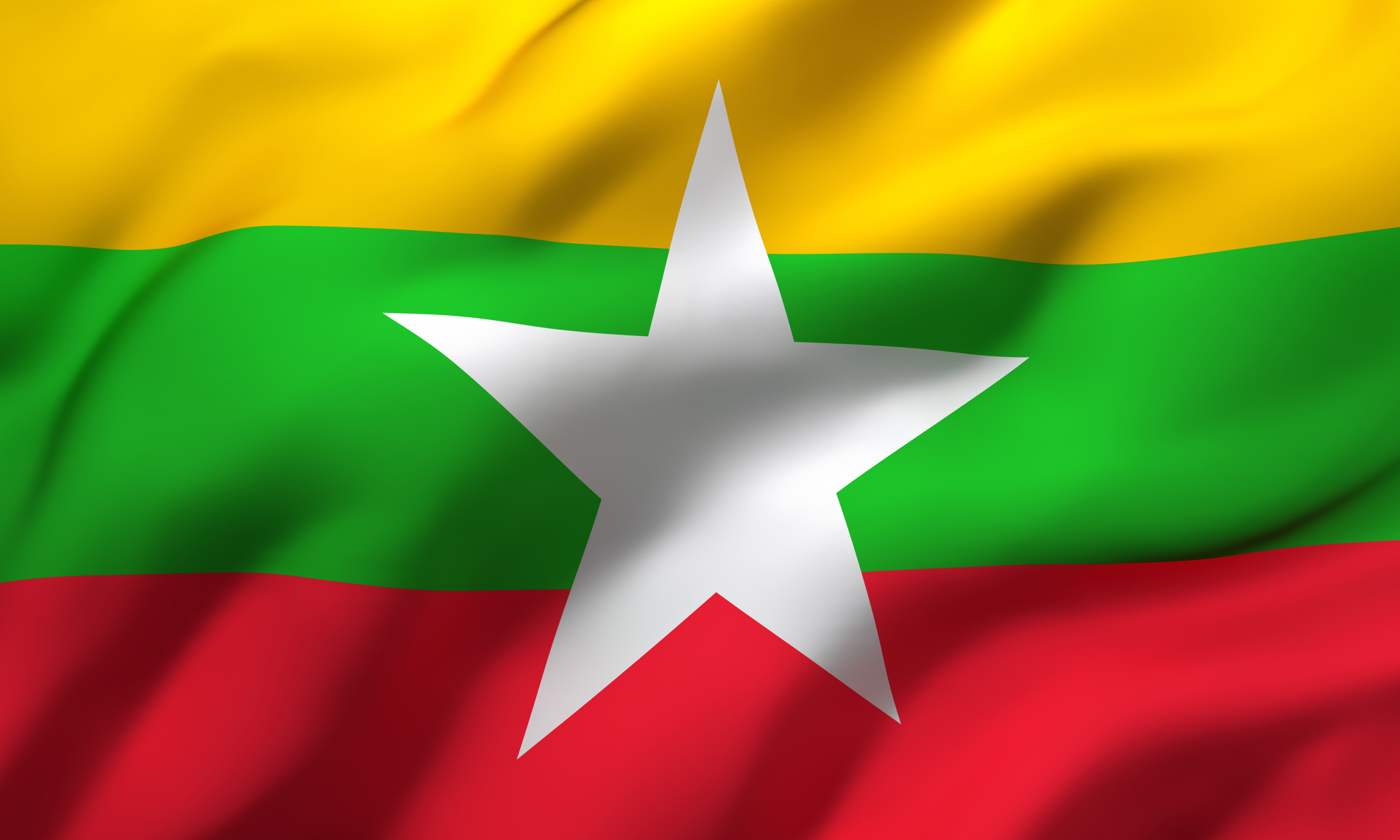 Flag of Myanmar blowing in the wind. Full page Myanma flying flag. 3D illustration.