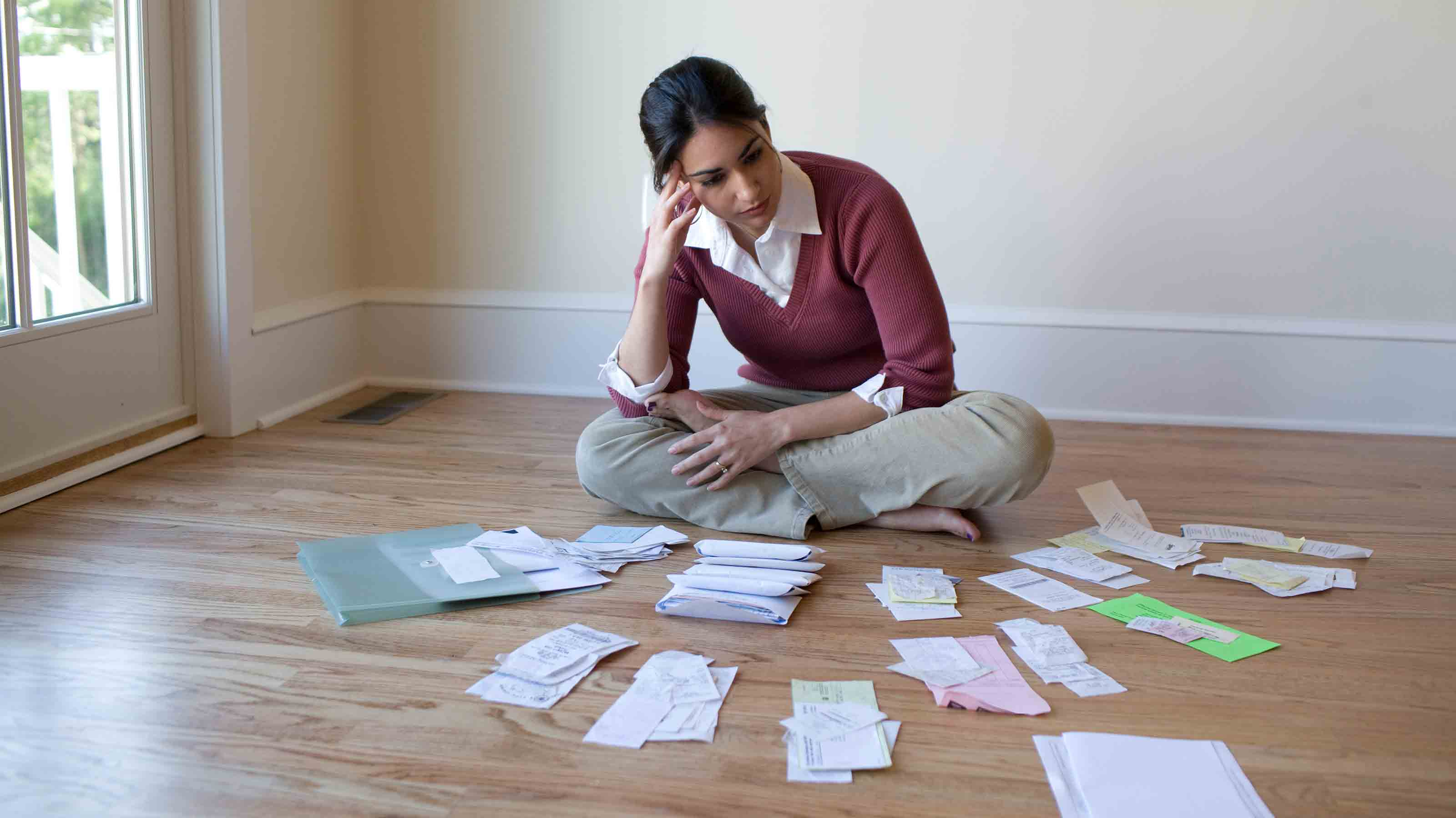 A young woman sitting on the floor looking at piles of receipts.