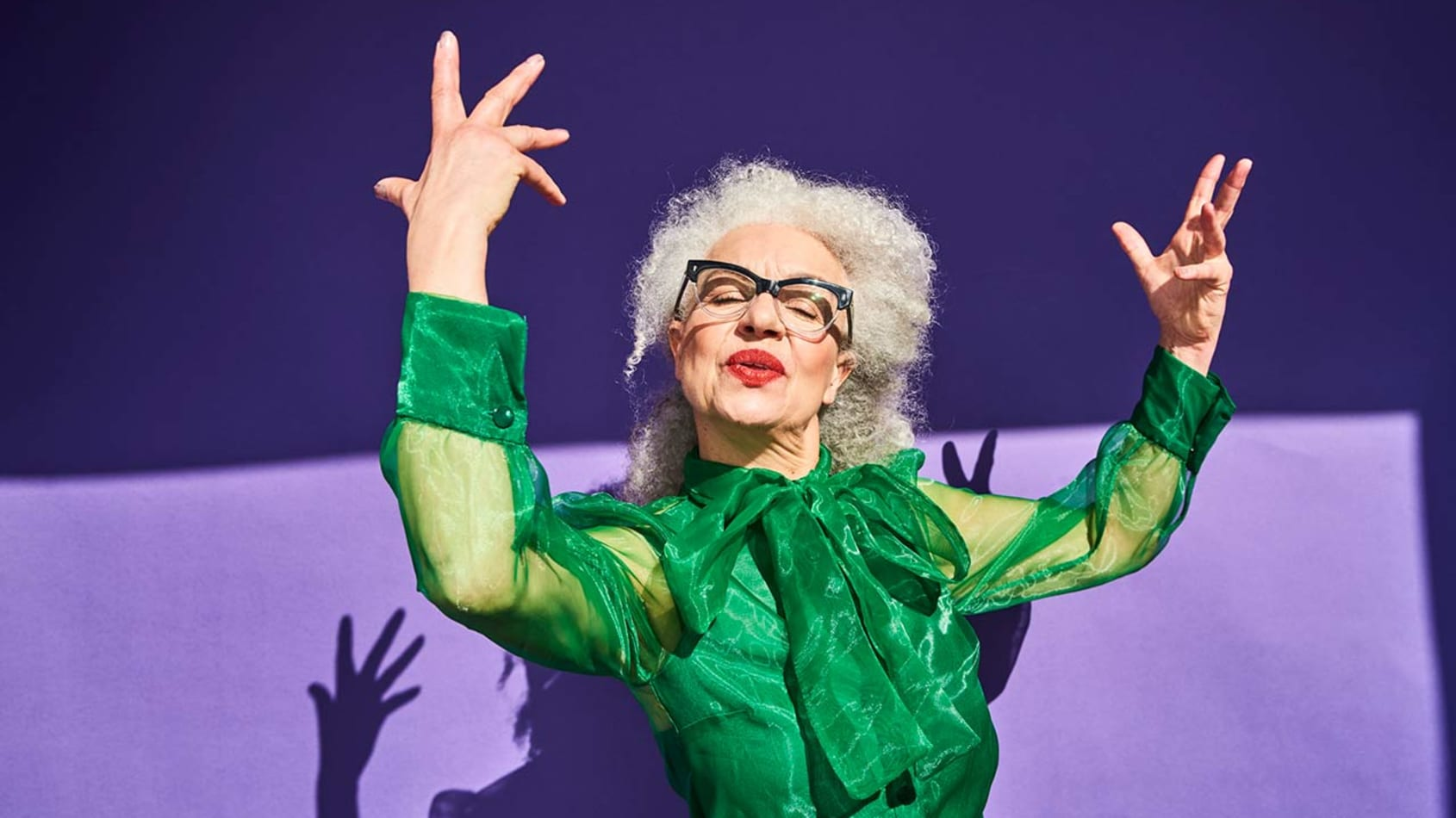 A senior woman in a bright green blouse with her hands in the air.