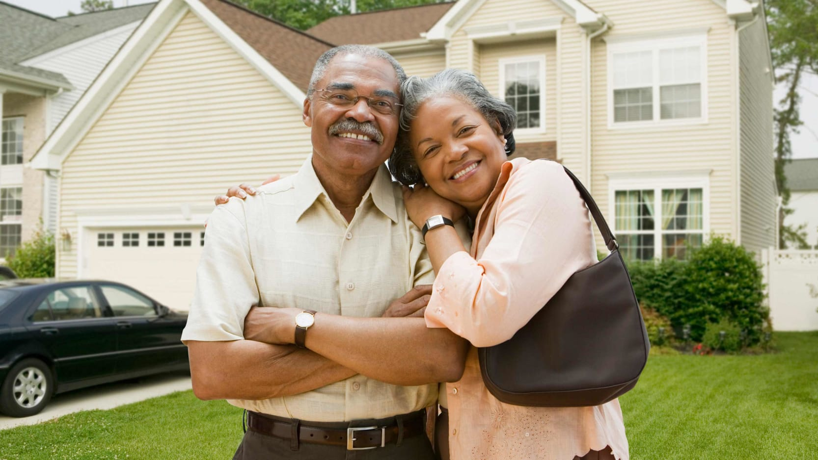 Senior couple in front of a new house.
