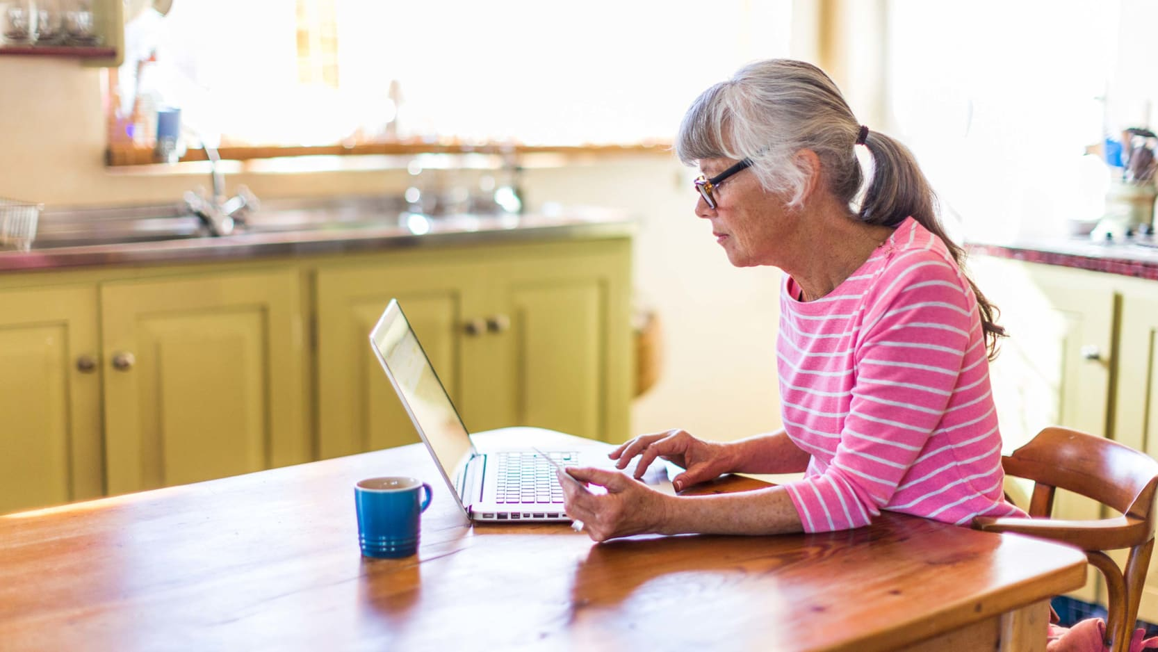 A senior woman sitting at her kitchen table working on her laptop.