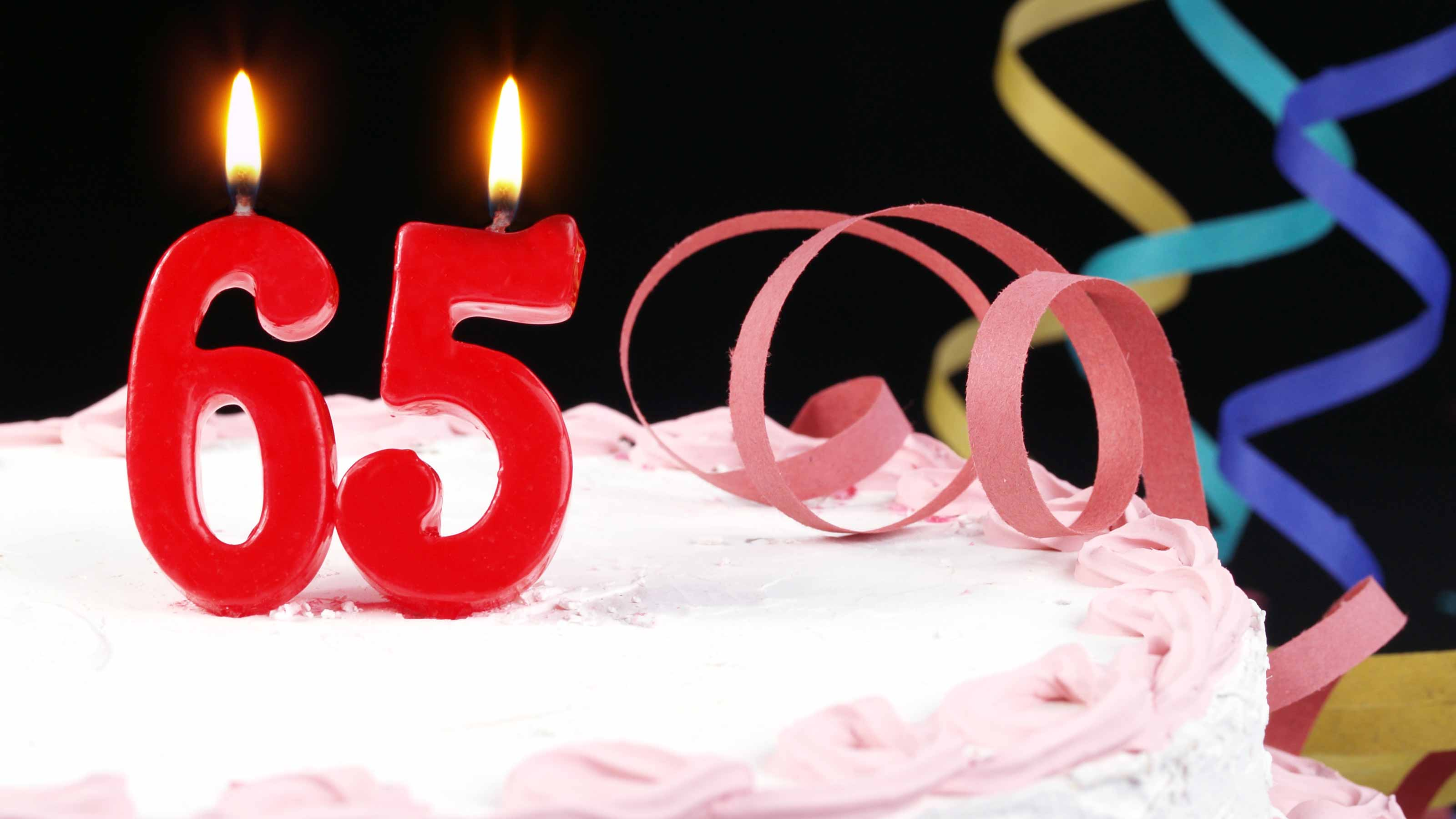 Birthday cake with candles showing the number 65.