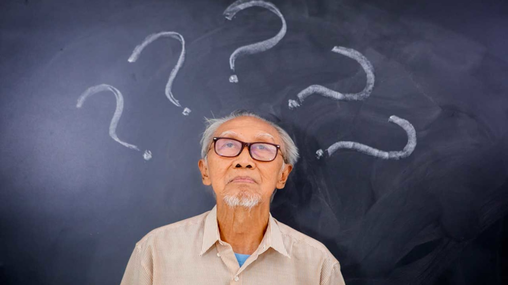 Senior man sitting in front of a blackboard with question marks surrounding his head.