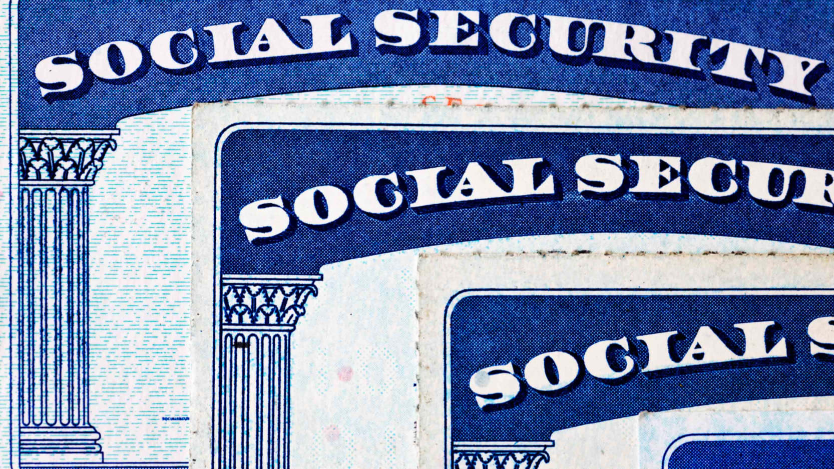 Three social security cards stacked on top of each other.
