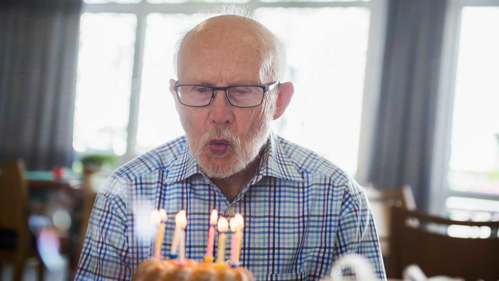 A senior man blowing out candles on a birthday cake.