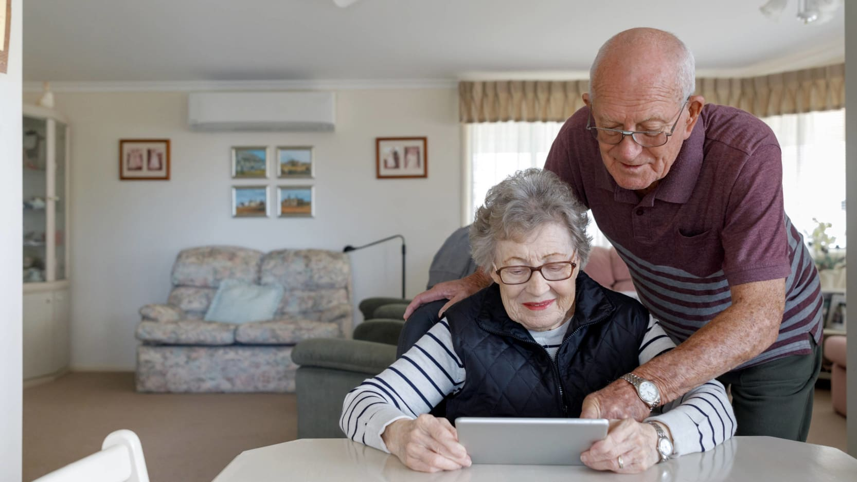 A senior woman at home sitting at a table looking at a tablet device. A senior man is leaning over her and pointing at the screen.