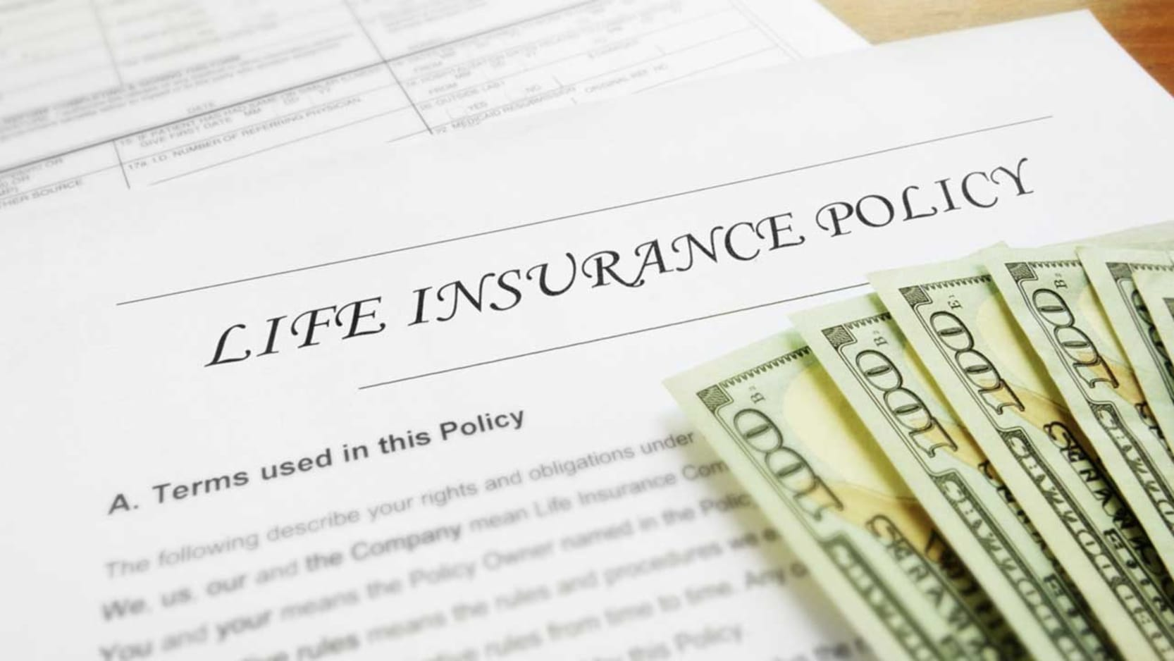 A life insurance policy on a desk with $100 bills lying on top.