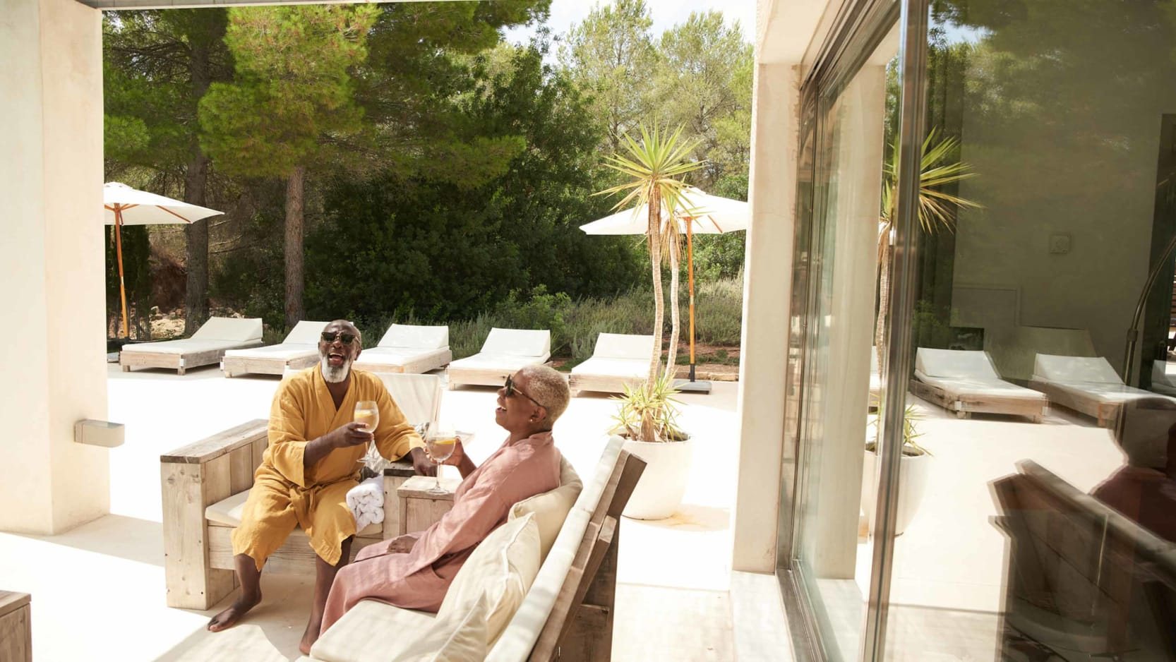 A senior couple sitting on a pool desk at a spa, wearing bathrobes, drinking wine and laughing.