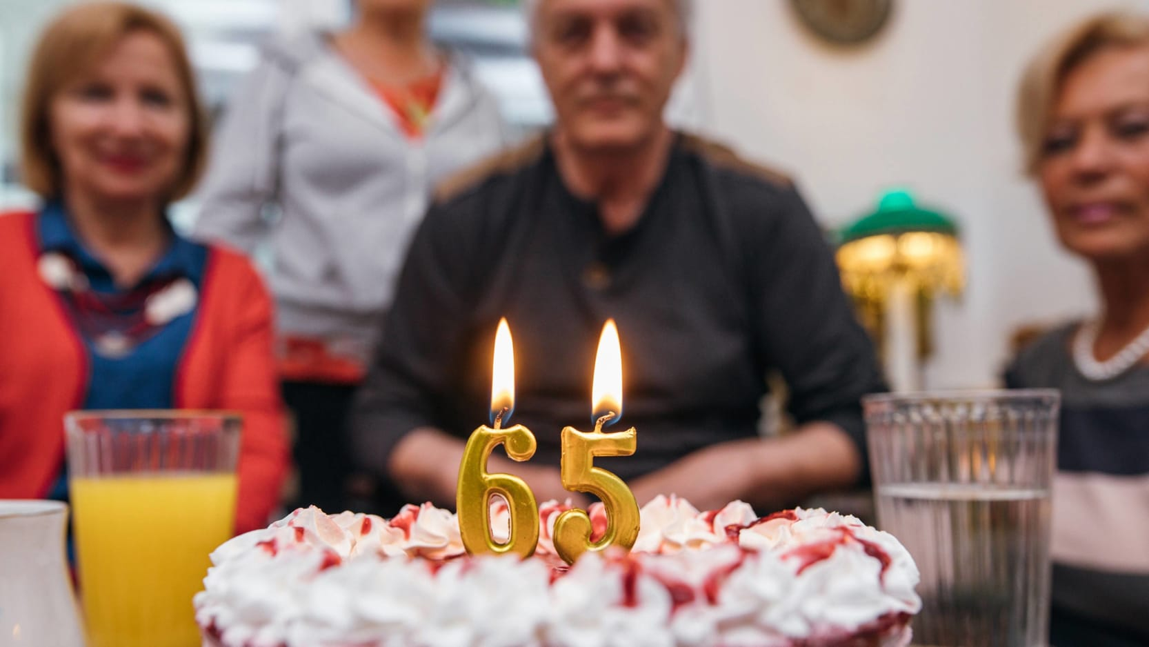 A senior man celebrating his 65th birthday with friends. There is a cake with candles saying 65.