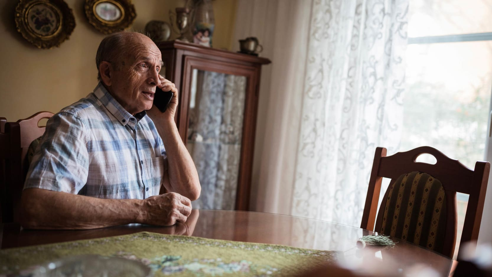 A senior man sitting at his dining room table speaking on his cellphone.