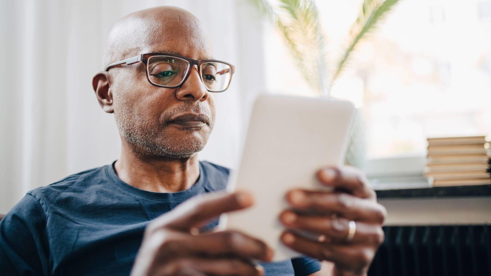 A senior man reading on a tablet device.