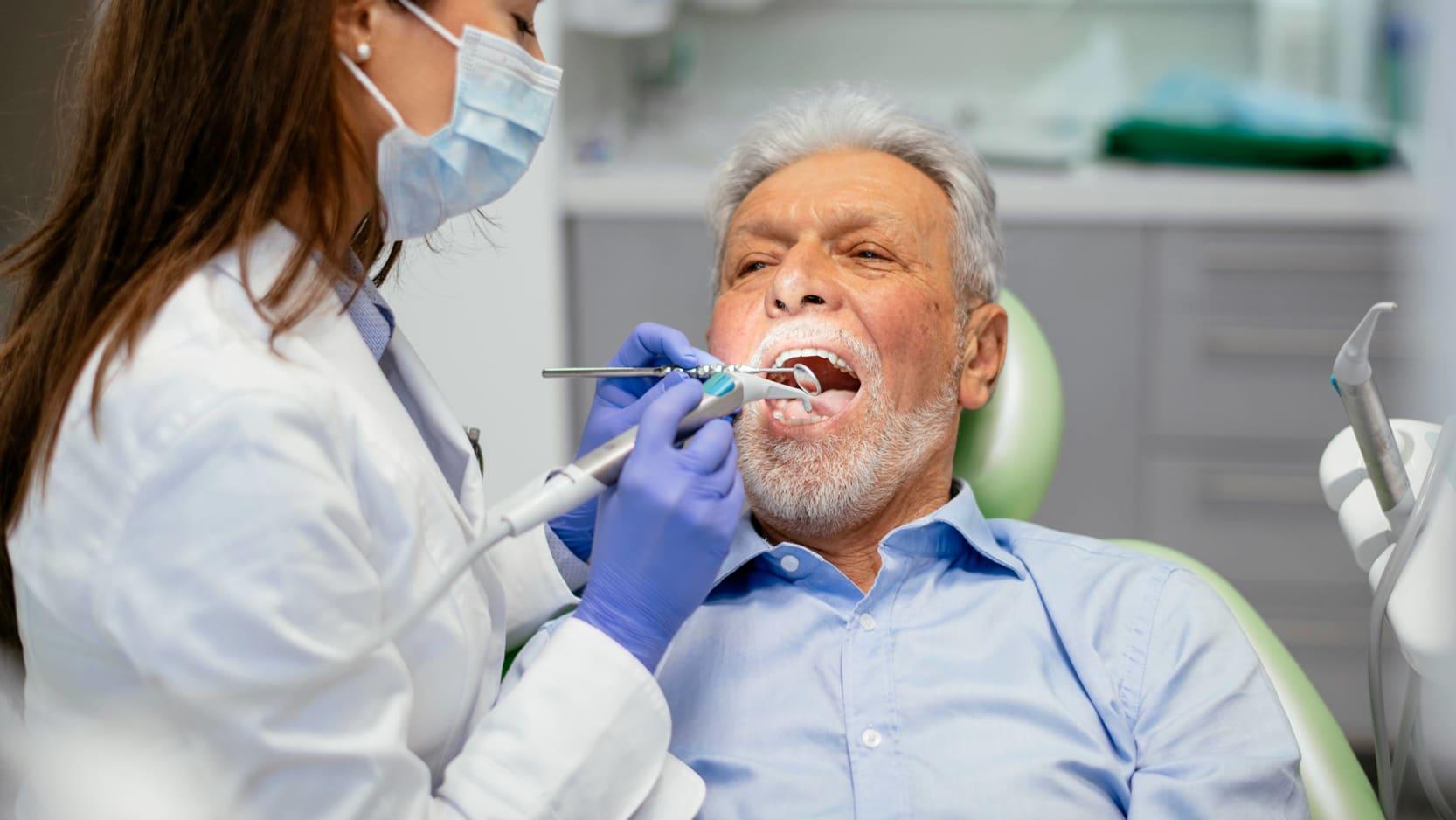 A senior man having his teeth cleaned.