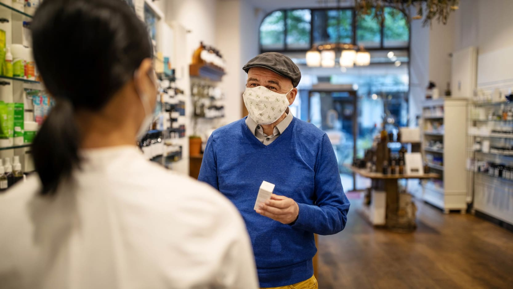 A senior man wearing a face mask speaking to a pharmacist.