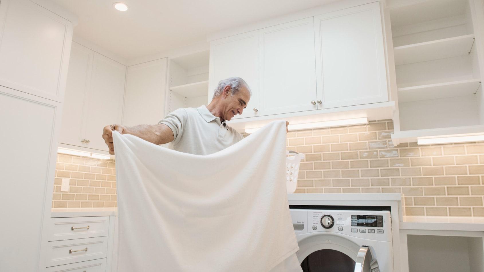 A senior man folding laundry in a laundry room.