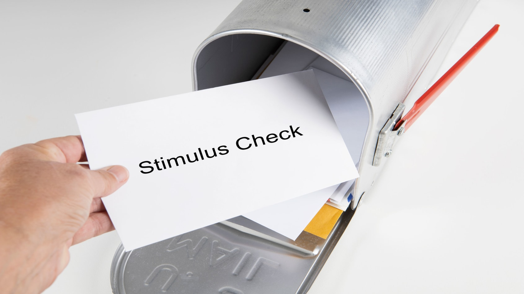 A hand pulling a letter out of a mailbox. The letter is labeled Stimulus Check.