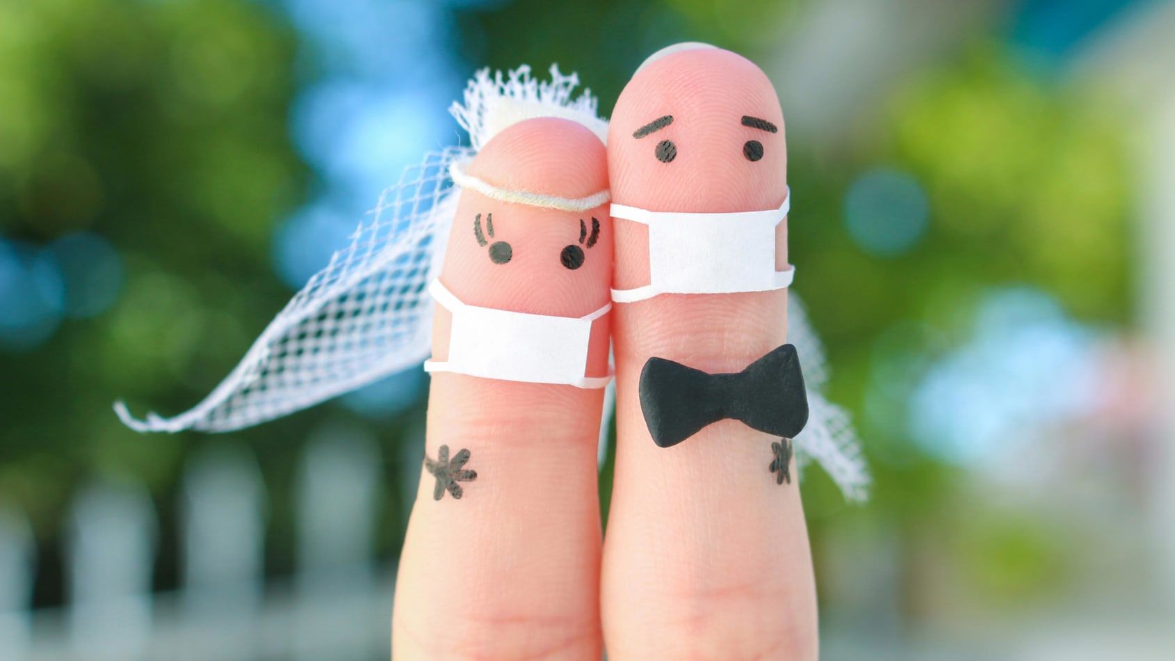 Two pointer fingers with drawn on faces getting married. Both are wearing masks.