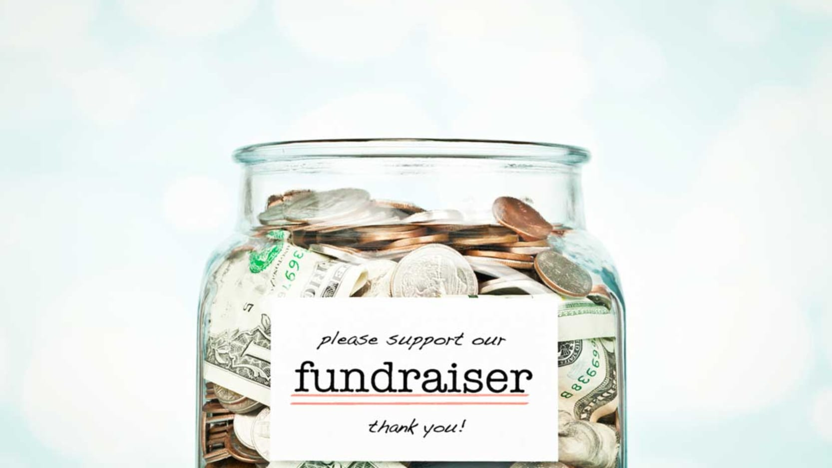 A glass jar full of coins with a label that reads Please support our fundraiser. Thank you!