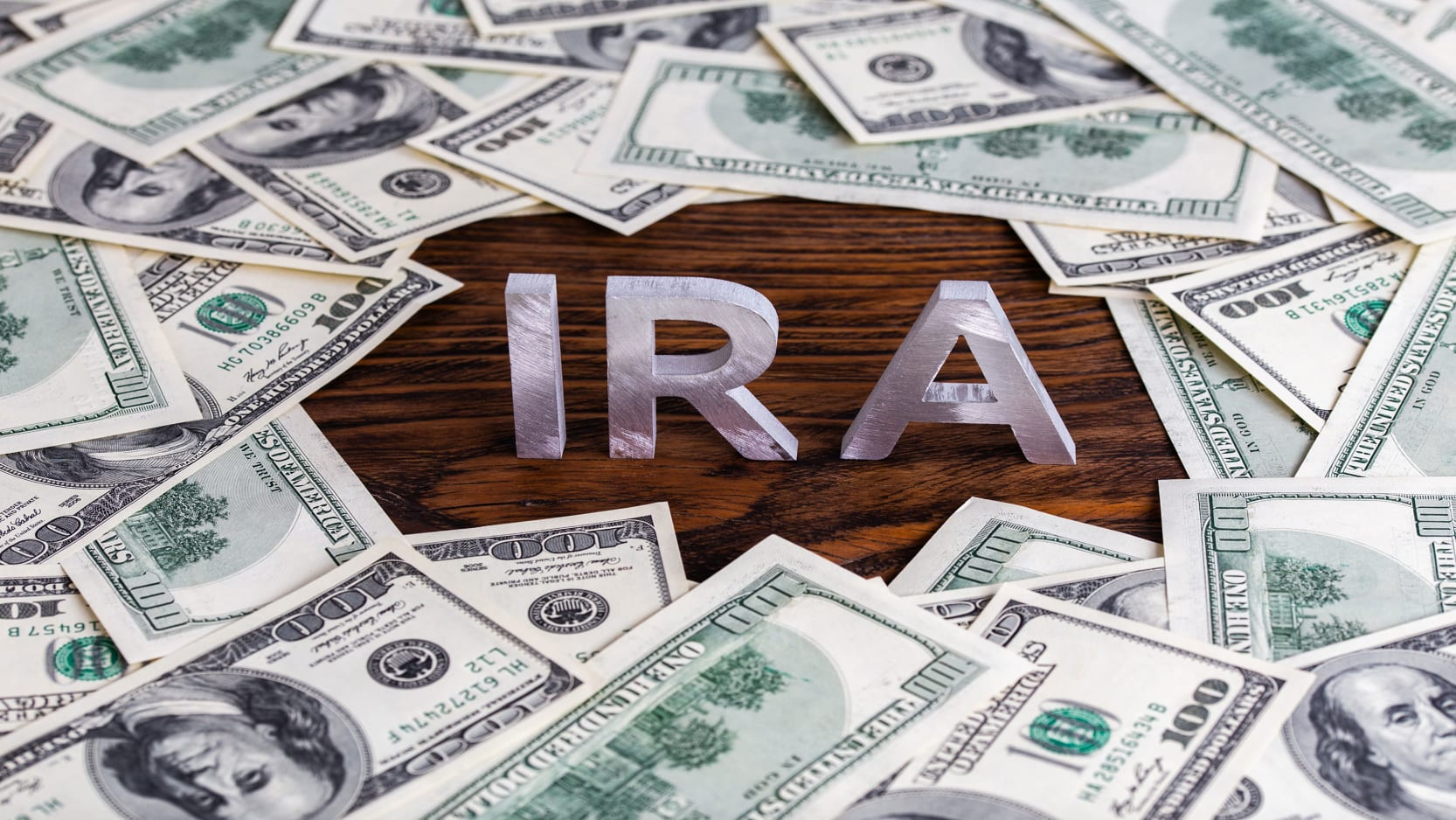 The letters IRA on a desk surrounded by $100 bills.