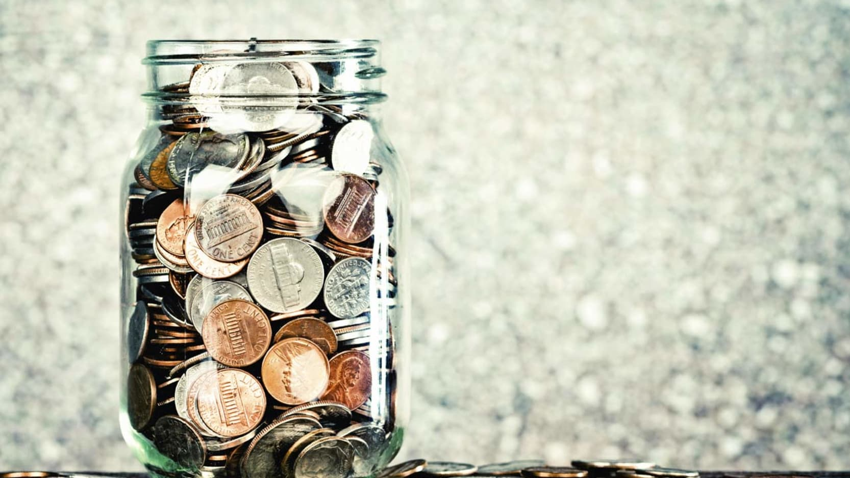 A glass jar filled with US coins.