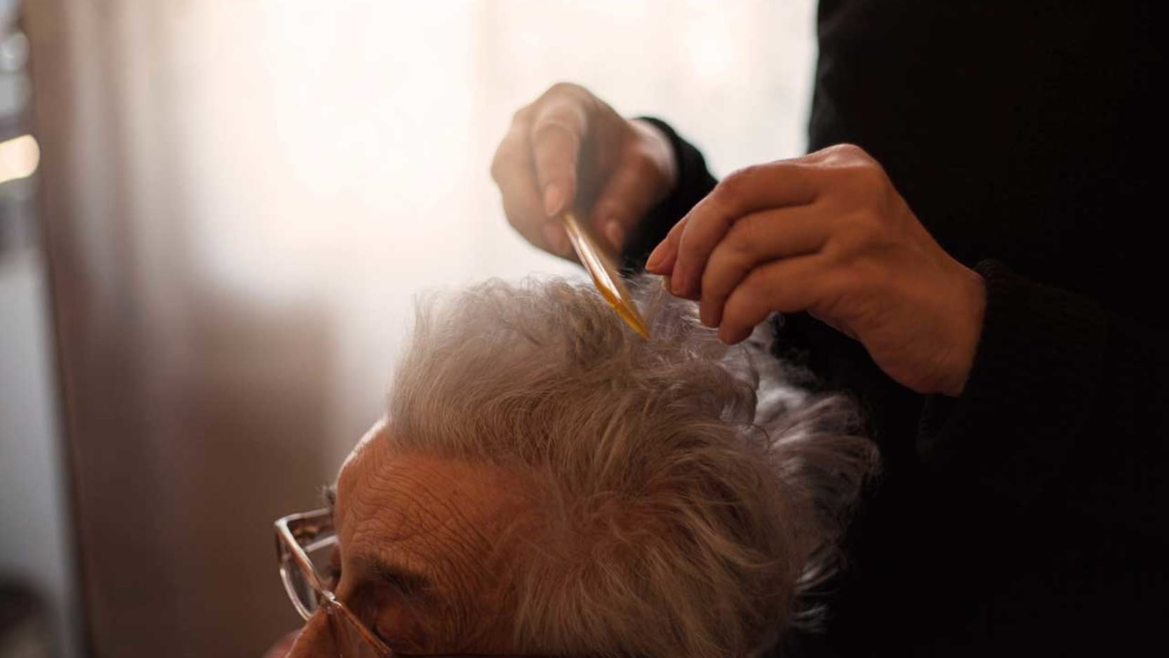 A senior man having his haircut by his daughter.