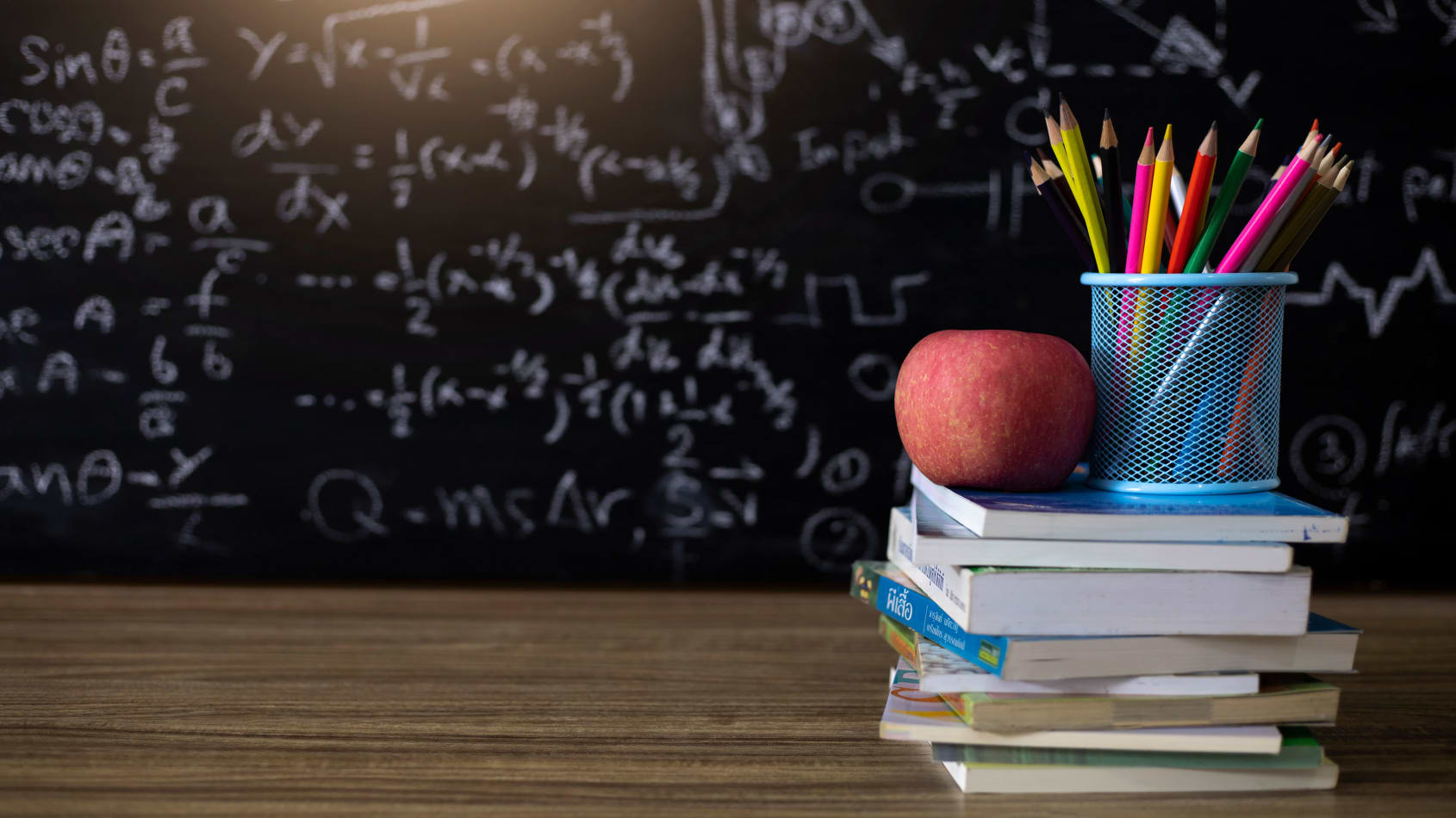 A stack of books and an apple on a desk in front of a blackboard.