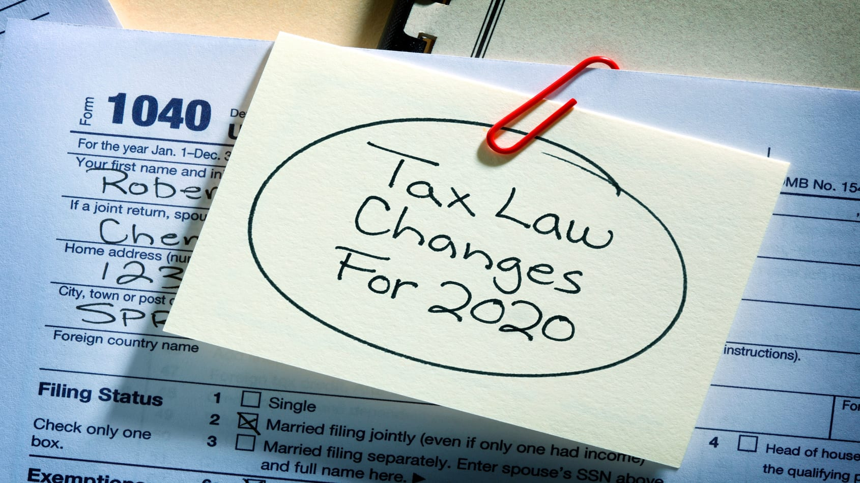 A 1040 tax form with a post-it note that has Tax Law Changes for 2020 written on it.