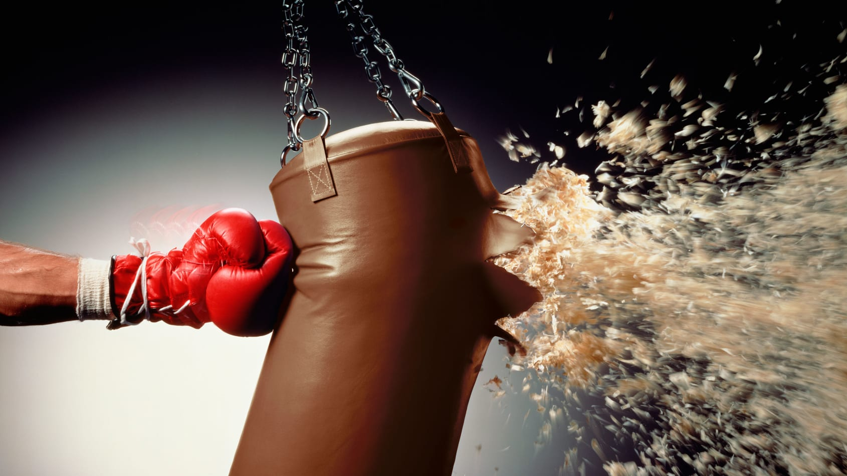 Man's arm punching a punching bag that's exploding.