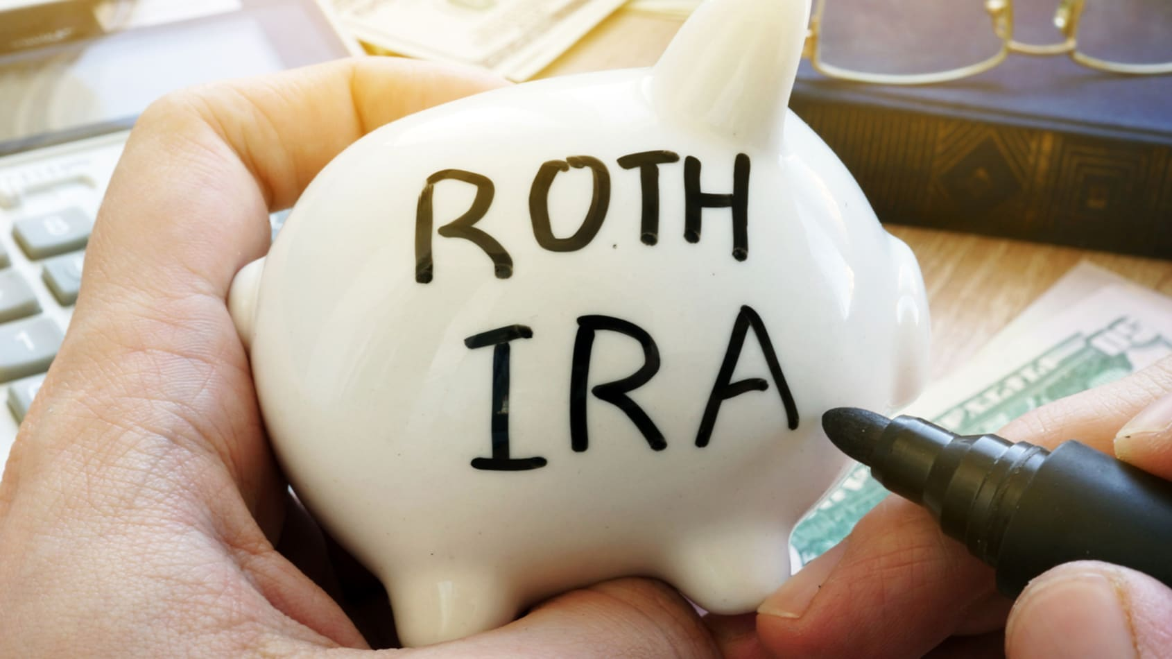 a person holding a small white piggy bank, writing Roth IRA in black Sharpie.