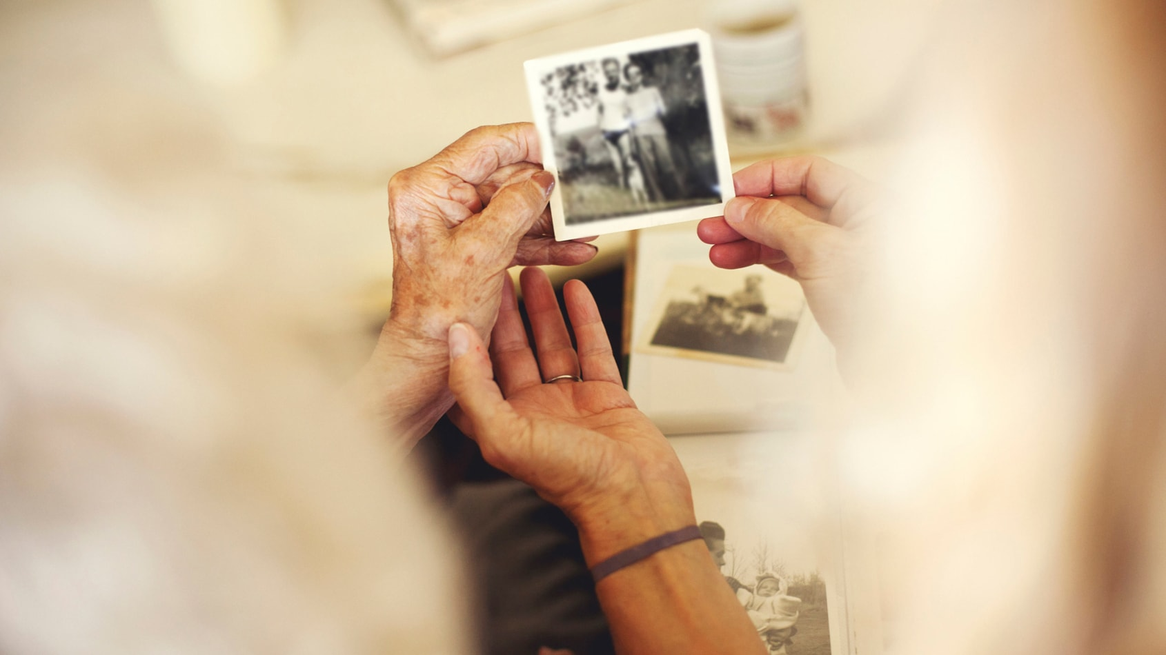Close up of aging hands holding old photo