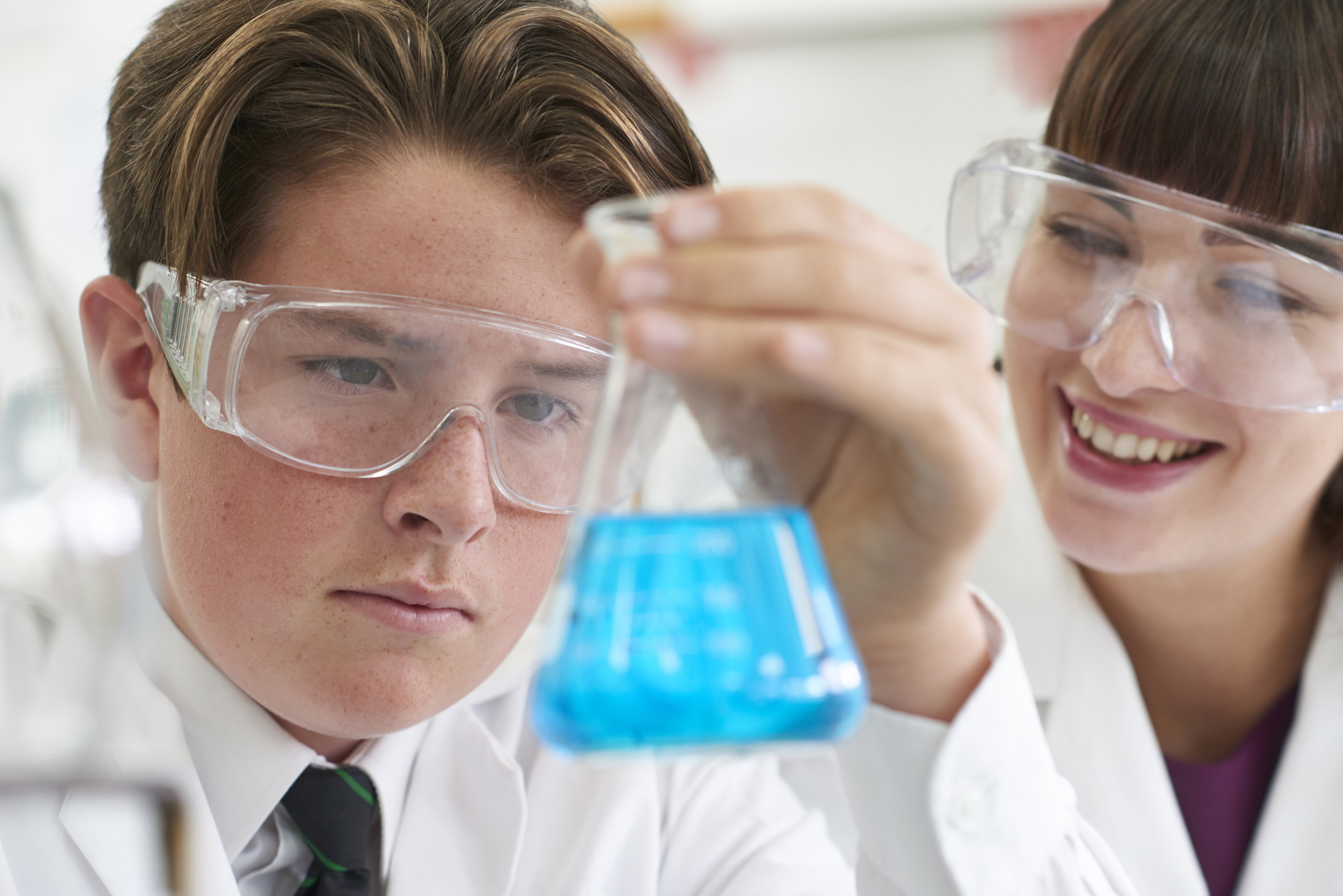 young student participating in a chemistry class, he has a beaker in his hand