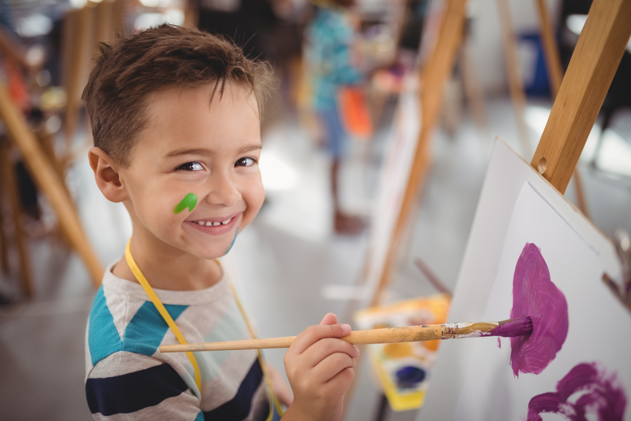 young student smiles while he paints