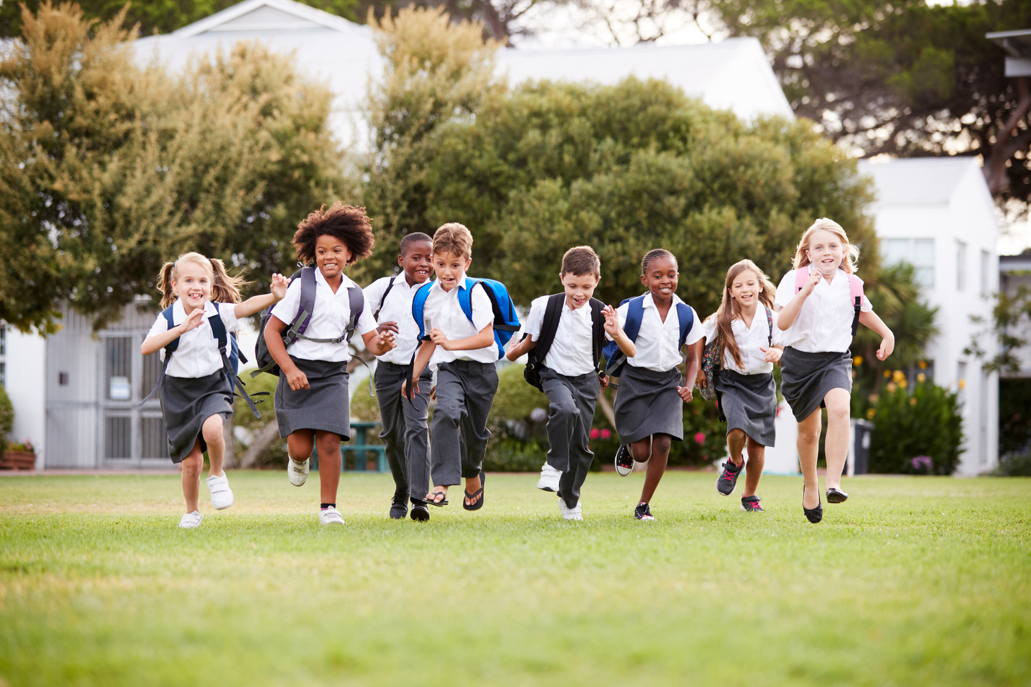 a large group of happy students run across a playing field