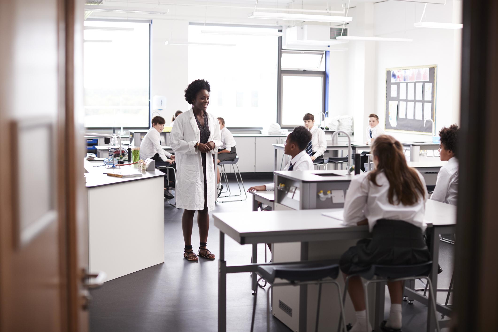 teacher wearing a lab coat teaching in a science class