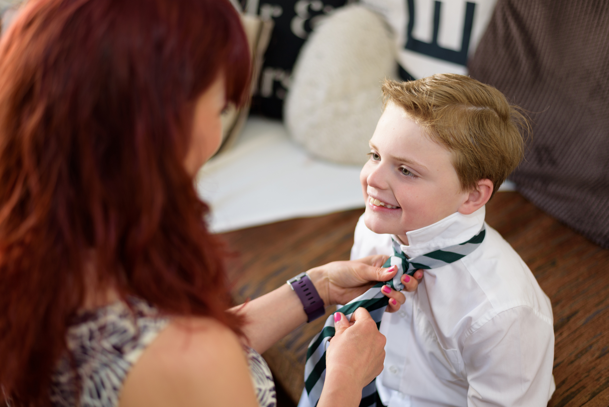 happy student is puting on his tie with the help of his mother