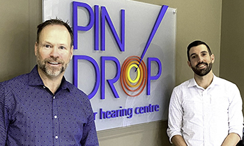 Pindrop Hearing staff in front of Pindrop logo/sign