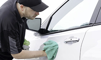 Employee from Wash King wiping down a vehicle