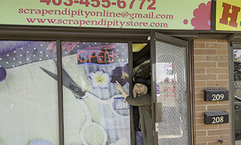 Scrapendipity employee pointing to sign that say Open