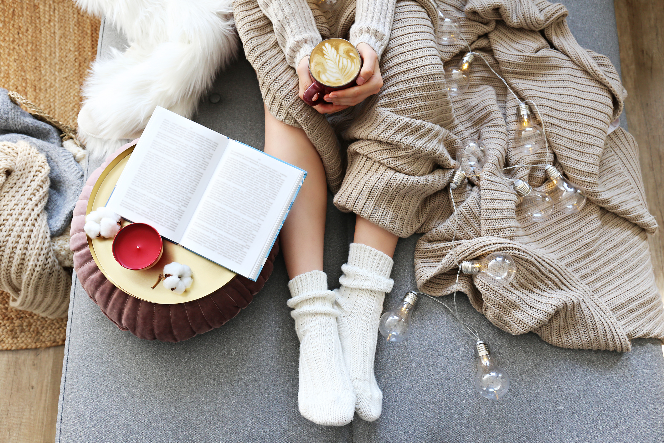 woman cosy reading a book with a cup of coffee