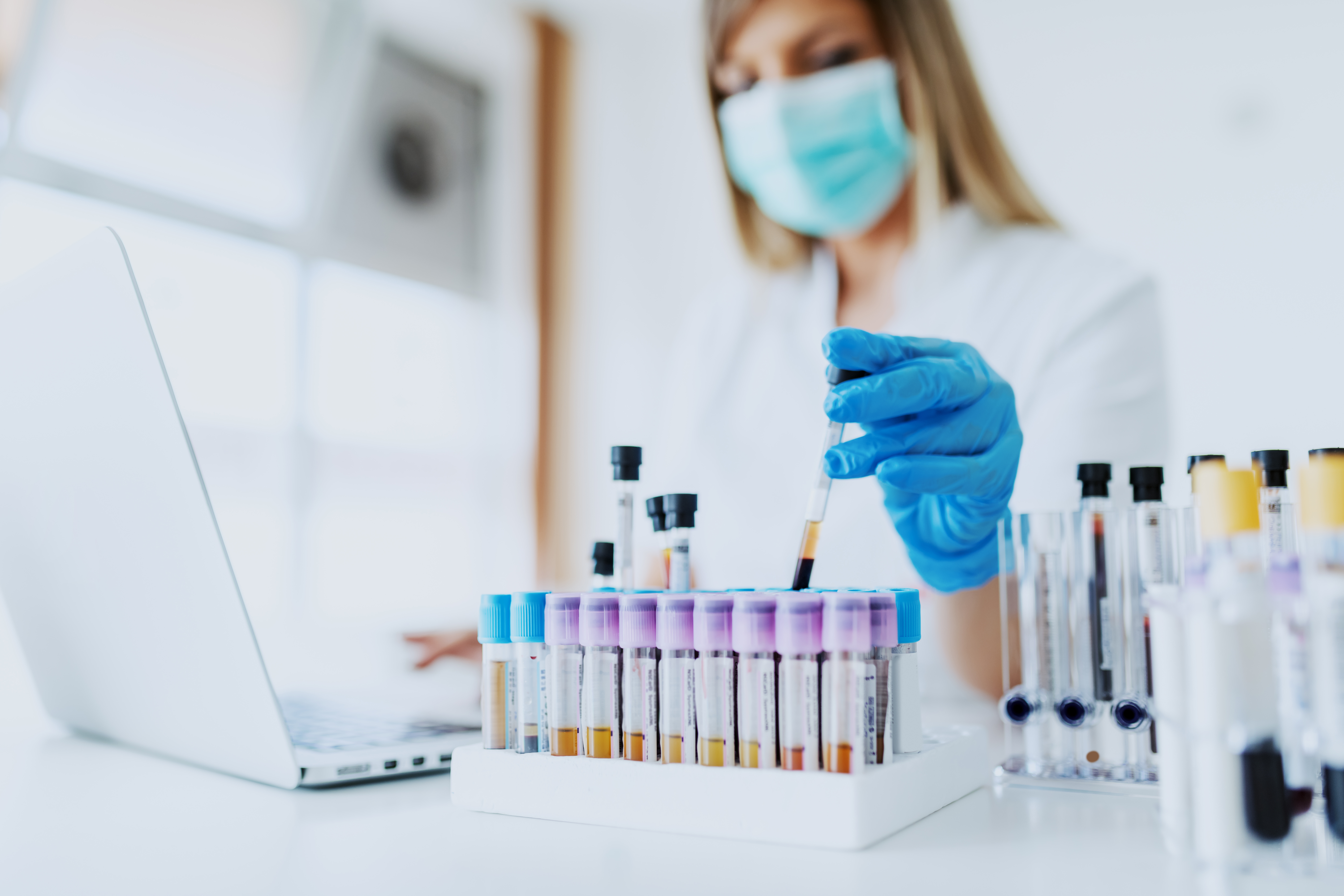 Close up of lab assistant in uniform, with mask and rubber gloves holding test tube with blood sample while sitting on chair and typing on laptop. Selective focus on test tubes.