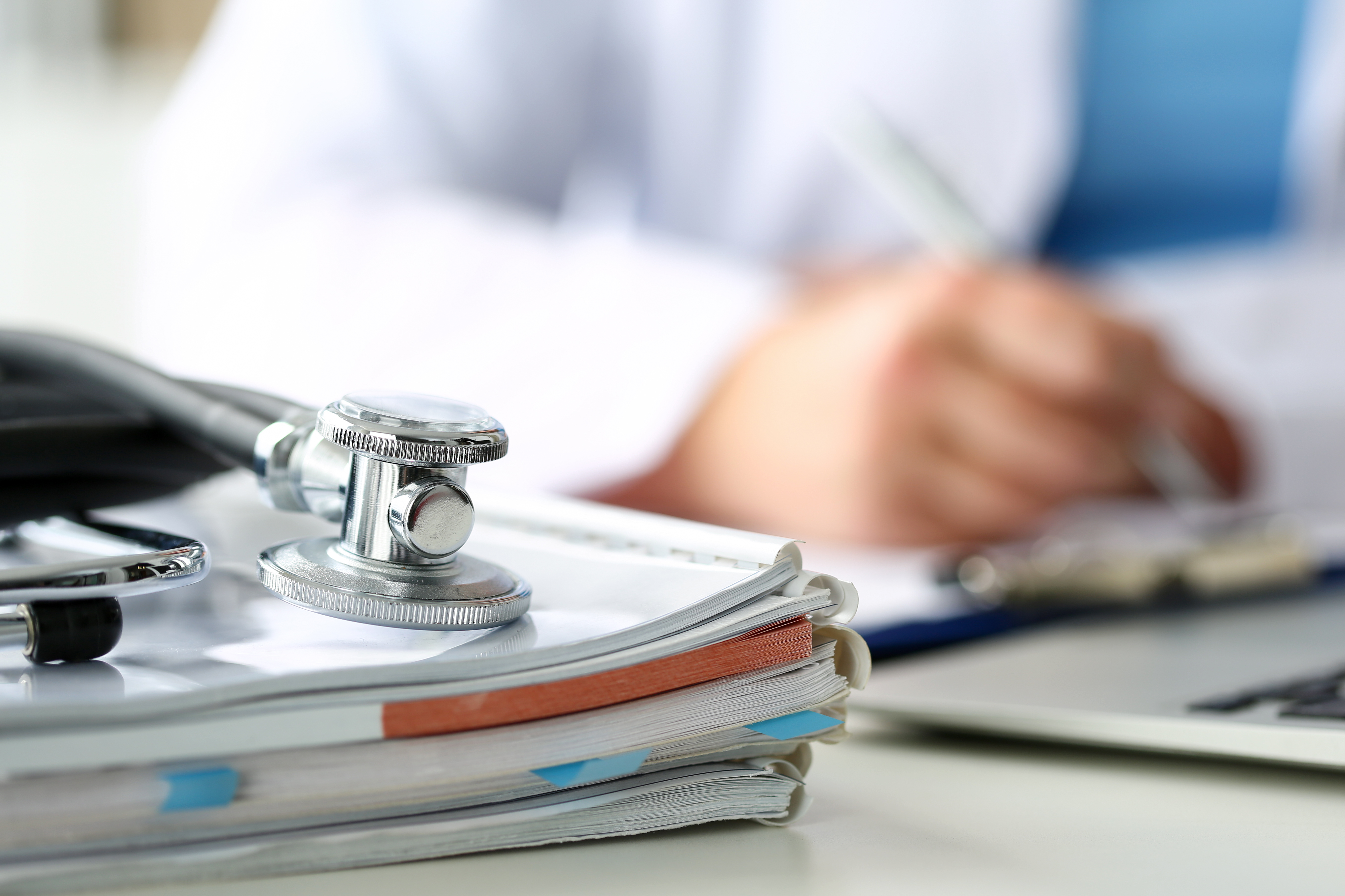 Stethoscope head lying on medical forms on clipboard closeup while medicine doctor working in background. Patient history list, visit check, 911, medical calculation and statistics, healthy lifestyle concept
