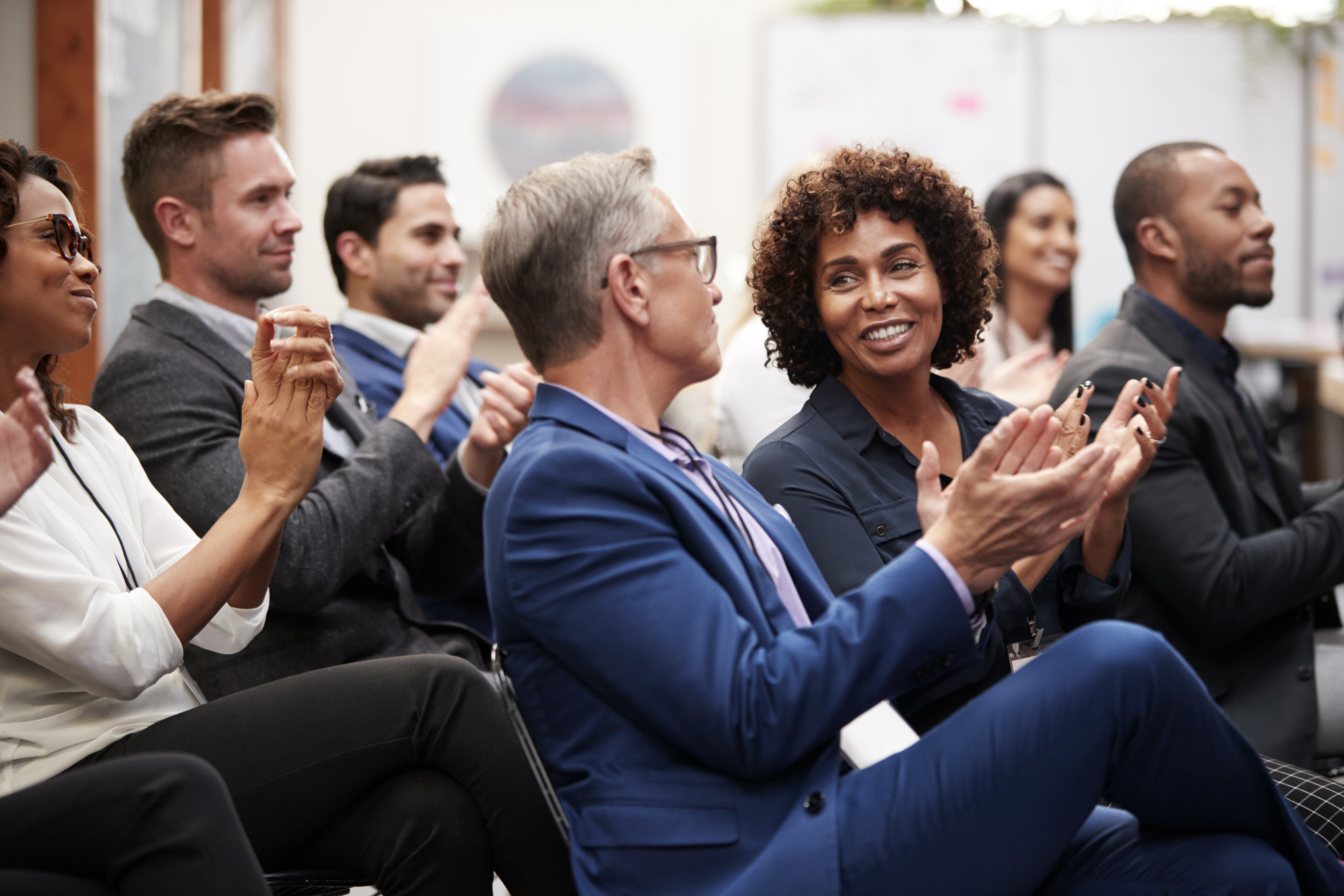 Group Of Businessmen And Businesswomen Applauding Presentation At Conference