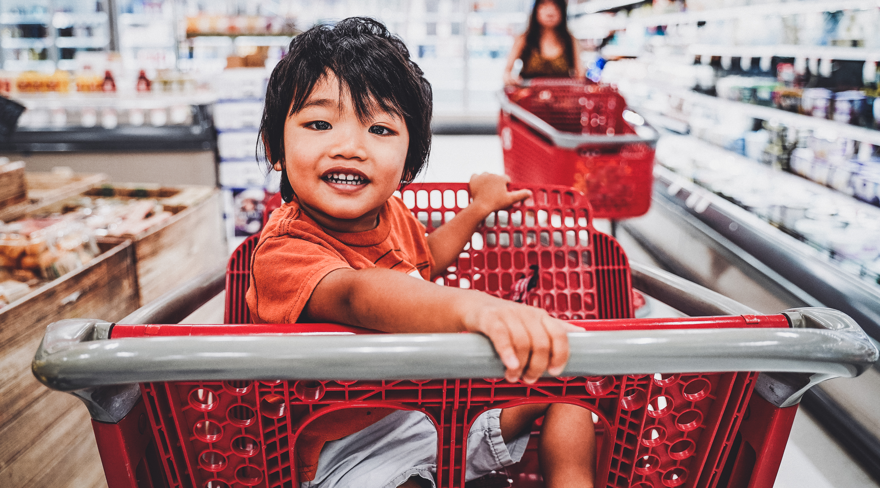 Close up photo of a child sitting in the seat of a shopping cart inside a grocery store. The child is looking directly at the camera and smiling